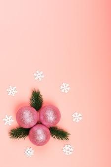 創造的なクリスマスのミニマルな構成。ピンクの背景にクリスマスボール。クリスマスツリーの枝とピンクのキラキラクリスマスのおもちゃ。上面図、フラットスタイル、テキスト用の空の場所