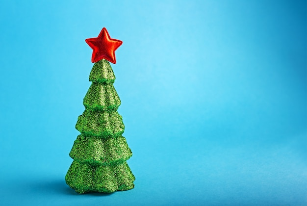 Creative christmas new year tree miniature with red star on top on blue color background with creative glitter sequins xmas tree and copy space.