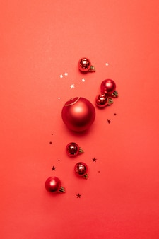 Creative christmas poster of red balls and glitter red stars on red . flat lay, top view, copyspace