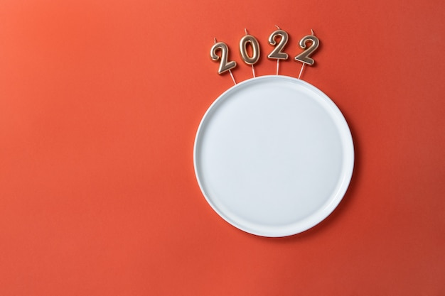 Creative christmas table setting. empty plate with straight edges, candles in form of numbers 2022, on red background, copy space, minimal layout, mockup. concept for festive menu, diet, food.