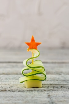Creative christmas tree of cucumber, cheese and star of carrot. funny kids food for new year party on grey background with copy space