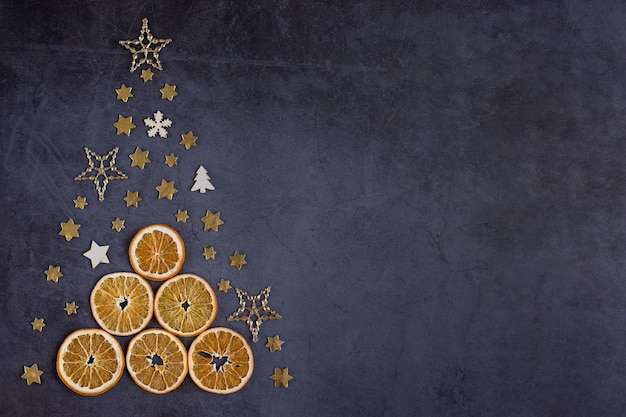 텍스트를 위한 어두운 배경 공간에 장식용 작은 액세서리로 만든 창의적인 크리스마스 트리