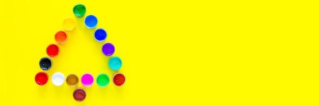 Креативная новогодняя елка из банок с краской на желтом фоне с местом для текста вид сверху fla ...