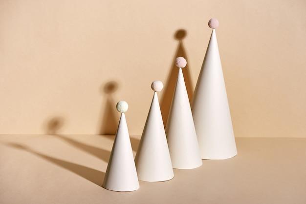 ベージュの背景に紙で作られた創造的なクリスマスツリー