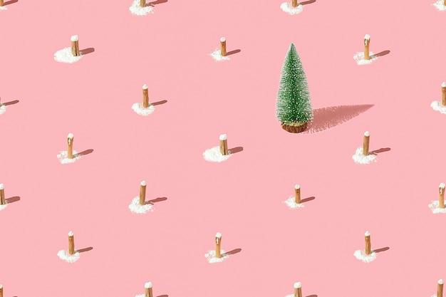 ピンクの背景に切り株を持つ創造的なクリスマスツリーのパターン。