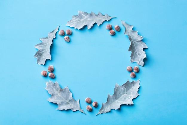 装飾的な乾燥した葉を持つ創造的なクリスマス冬秋秋の日の構成。フラットレイ、上面図、コピースペース、グリーティングカードの静物ブルーパステル背景