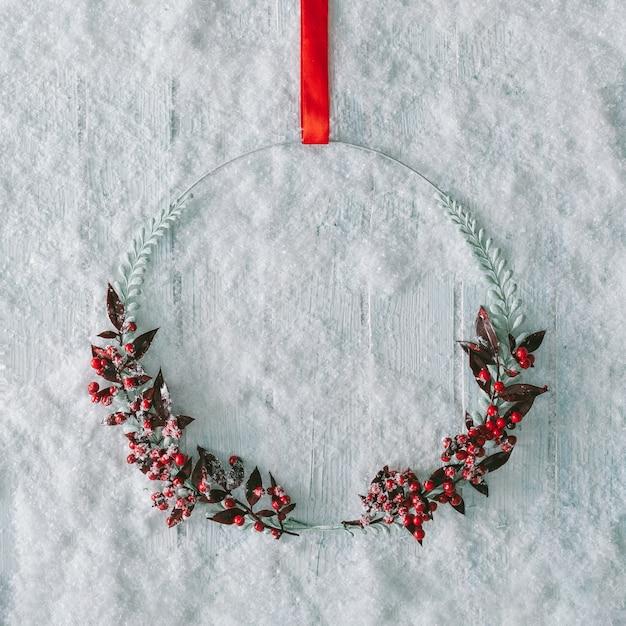 눈 흰색 나무 테이블에 크리 에이 티브 크리스마스 겨울 장식. 최소한의 자연 화환.