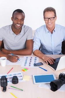 Творческие сотрудники за работой. вид сверху двух веселых деловых людей в повседневной одежде, сидящих за столом и смотрящих в камеру