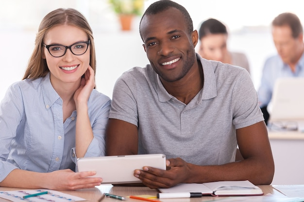 Творческие сотрудники. два деловых человека сидят вместе за столом и держат цифровой планшет, пока другие люди работают на заднем плане