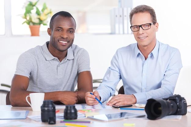 Творческие сотрудники. два веселых деловых человека в повседневной одежде сидят вместе за столом и смотрят в камеру