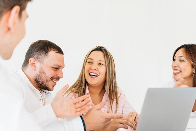 Творческие коллеги обсуждают и смеются в офисе