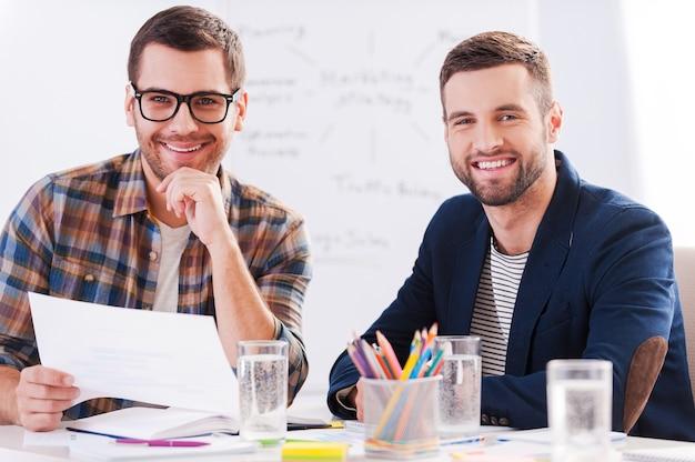 Творческие коллеги. два веселых бизнесмена в элегантной повседневной одежде сидят вместе за столом и смотрят в камеру