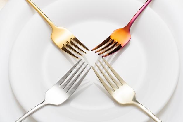 Креативные цветные металлические вилки на белой тарелке