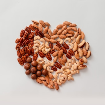 Creative composition of assorted walnut or mix nuts pecans, macadamis, brazil nut, cashews, almonds on a gray background. diet, proper balancing nutrition concept