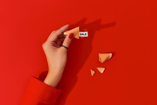 Creative composition for black friday shopping sale female hand with manicure holding fortune cookie