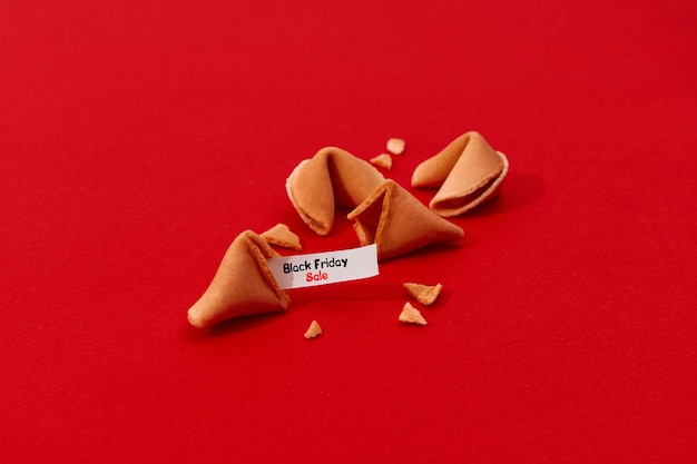 Creative composition for black friday shopping sale fortune cookies on red