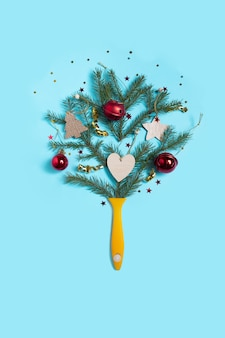 창의적인 구성 크리스마스. 크리스마스 전나무와 빨간색 배경에 장식품 페인트 브러시.