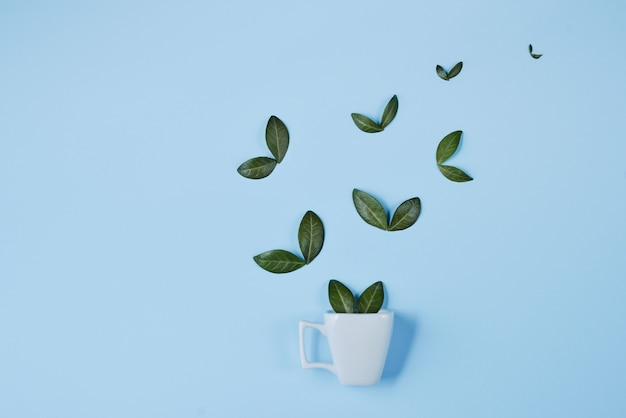 Creative composition. coffee cup with birds made of natural green leaves on blue background