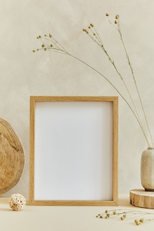 Creative composition of cozy minimalistic interior design with mock up poster frame, natural materials as wood and marbel, dry plants and personal accessories. neutral beige colors, template.