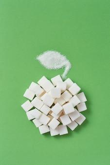 달콤한 설탕의 다른 유형에서 수제 사과 과일에서 창조적 인 구성은 큐브와 밝은 녹색 벽에 입자가 굵은 설탕에서 잎, 복사 공간. 평평하다.