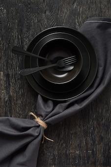 空の黒い台所用品からの創造的な構成-同じ色の背景、コピースペースにフォークとスプーンで提供されるテキスタイルナプキンを備えた皿と皿。上面図。