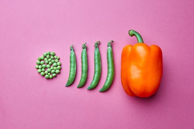 ピンクの背景に閉じたポッドと赤唐辛子でいっぱいの円の形のグリーンピースの粒からの創造的な構成。フラットレイ。食品の概念。
