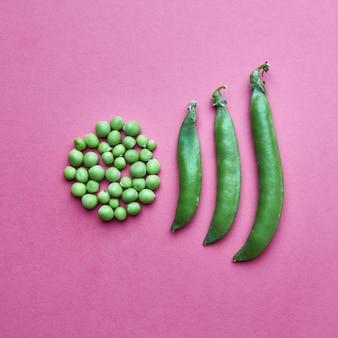 Креативная композиция из зерен зеленого горошка в виде круга и полных закрытых стручков