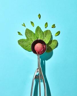 Креативная композиция из фруктов личи с листьями мяты в металлической ложке для мороженого на фоне синего стекла с тенями. еда в современном стиле, вид сверху.