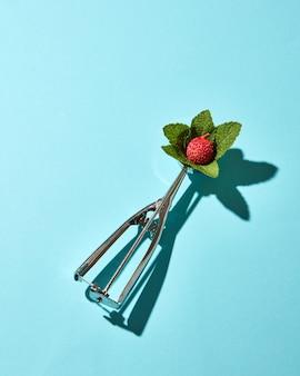 Креативная композиция из фруктов личи с листьями мяты в металлической ложке для мороженого на фоне синего стекла с тенями. еда в современном стиле.