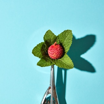 Creative composition from litchi fruit with mint leaves in the metal spoon for ice cream on a blue glass background with shadows. food modern style, top view.