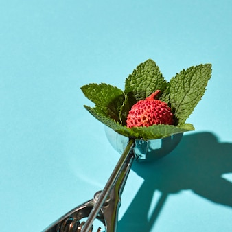 Creative composition from litchi fruit with mint leaves in the metal spoon for ice cream on a blue glass background with shadows. food modern style.