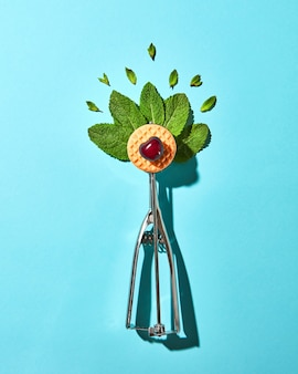 Creative composition from mint leaves in the metal spoon for ice cream and biscuit with cherry on a blue glass background with shadows. food modern style, top view.