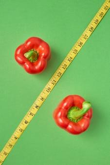 緑の背景にパーセントのシンボルとして2つの赤いパプリカペッパーと斜めの黄色の巻尺からの創造的な構成、コピースペース。上面図。軽量化のための低カロリー食品。