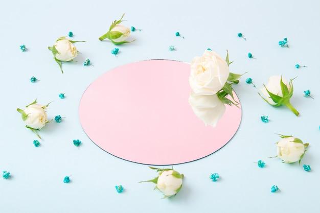 거울에 분홍색 반사가 있는 파스텔 파란색 배경에 흰색 장미와 파란색 꽃으로 만든 창의적인 구성. 최소한의 봄 꽃 개념입니다. 공간을 복사합니다.