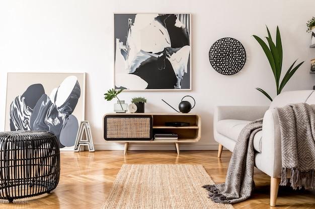 프레임, 목재 옷장, 소파 및 액세서리가있는 아늑하고 세련된 거실 인테리어 디자인의 창의적인 구성. 흰 벽과 쪽모이 세공 마루 바닥. 중성 색상.