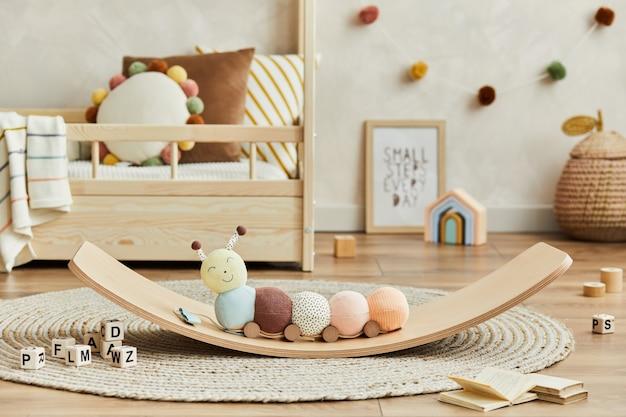 バランスボードに豪華な毛虫、木のおもちゃ、テキスタイルの装飾が施された、居心地の良いスカンジナビアの子供部屋のインテリアのクリエイティブな構成。中立的な壁、床にカーペット。詳細。レンプレート。