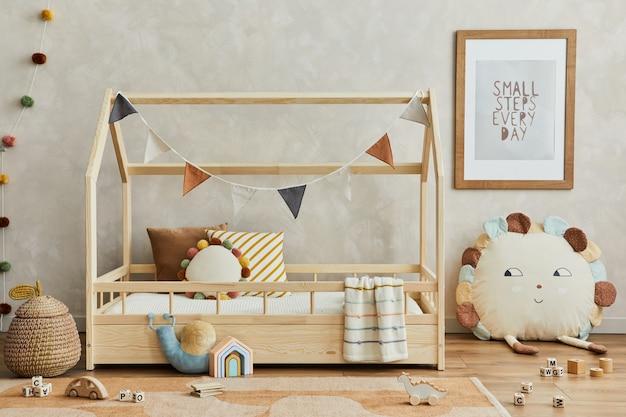 木製のベッド、枕、ぬいぐるみ、木のおもちゃ、テキスタイルの吊り下げ装飾が施された、居心地の良いスカンジナビアの子供部屋のインテリアのクリエイティブな構成。ニュートラルなクリエイティブな壁、床にカーペット。レンプレート。