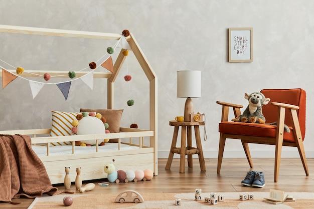 木製のベッド、赤いアームチェア、ぬいぐるみと木のおもちゃ、テキスタイルの吊り下げ装飾が施された、居心地の良いスカンジナビアの子供部屋のインテリアのクリエイティブな構成。創造的な壁、床のカーペット。レンプレート。