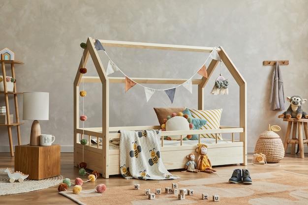木製の家具、豪華な木製のおもちゃ、テキスタイルの吊り下げ装飾が施された、居心地の良いスカンジナビアの子供部屋のインテリアのクリエイティブな構成。ニュートラルなクリエイティブな壁、床にカーペット。レンプレート。
