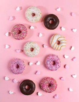 Творческий состав пончиков с разноцветной глазурью и маленькими зефирами в форме сердца на модном розовом фоне.