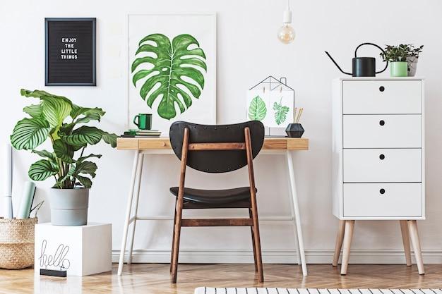 Креативная композиция дизайна интерьера домашнего рабочего пространства с рамкой для плаката, столом, растениями в хипстерских горшках и аксессуарами