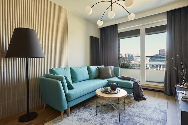 小さなアパートのモダンなリビングルームのインテリアの創造的な構成。ユーカリのソファ、黒いランプ、コーヒーテーブル、身の回り品。大都会の景色を望む窓。レンプレート。
