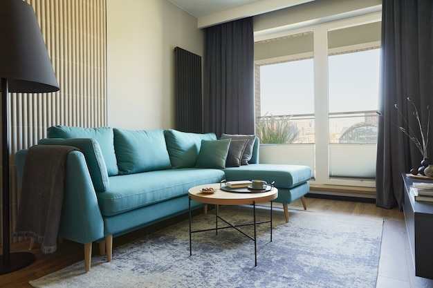 小さなアパートのモダンなリビングルームのインテリアの創造的な構成。ユーカリのソファ、コーヒーテーブル、身の回り品。大都会の景色を望む窓。レンプレート。