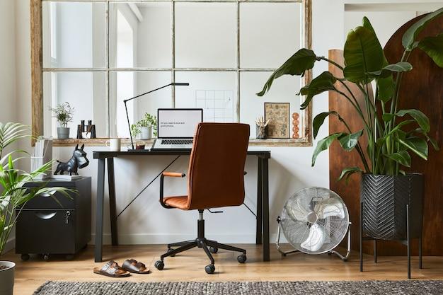 黒の工業用デスク、茶色の革張りのアームチェア、ラップトップ、スタイリッシュなパーソナルアクセサリーを備えた、モダンで男性的なホームオフィスのインテリアデザインのクリエイティブな構成。レンプレート。