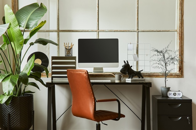 黒の工業用デスク、茶色の革張りのアームチェア、pc、スタイリッシュなパーソナルアクセサリーを備えた、モダンで男性的なホームオフィスワークスペースのインテリアデザインのクリエイティブな構成。レンプレート。
