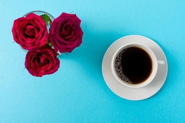 Творческий состав цветка красной розы и чашки кофе на синем фоне.