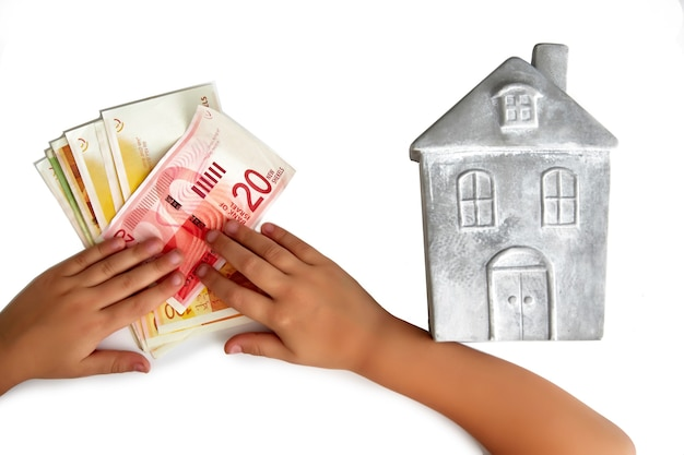 돌 모형 집과 아이가 흰 벽에 이스라엘 새 셰켈 더미를 들고 창의적인 구성