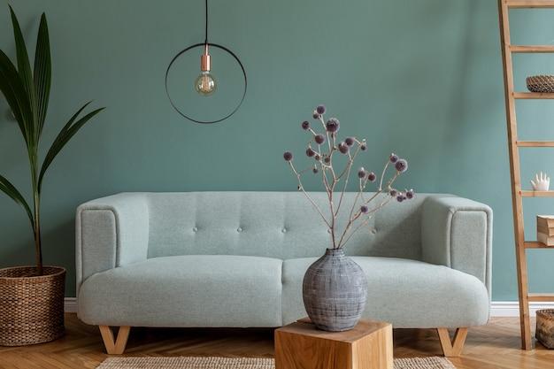 Креативная композиция стильного и уютного интерьера гостиной с копией пространства, зеленой стеной, диваном из эвкалипта, ковром, журнальным столиком, растением, книгами и современным декором. паркетный пол.