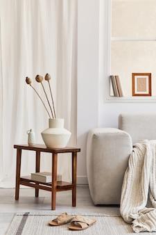 Креативная композиция стильного и уютного интерьера гостиной с макетной рамой, серым угловым диваном, окном, засушенными цветами на журнальном столике и личными аксессуарами. бежевые нейтральные цвета. шаблон.