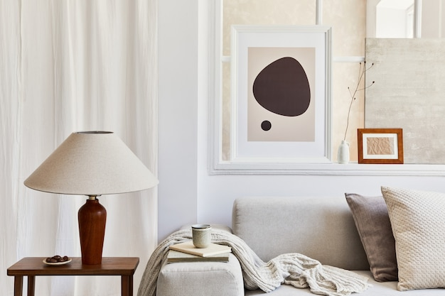 모의 포스터 프레임, 회색 소파, 램프, 창문, 격자 무늬, 베개 및 개인 액세서리가 있는 세련되고 아늑한 거실의 창의적인 구성. 베이지색 중성 색상입니다. 주형.